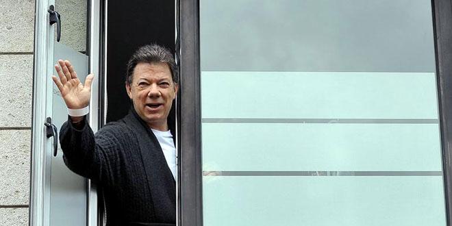 Juan Manuel Santos saluda desde la ventana de la clinica donde fue intervenido