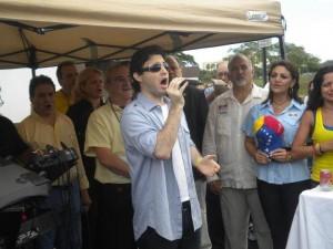 El joven Edward Mena junto a sus compatriotas entona el himno nacional